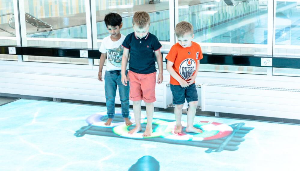 Kolme poikaa pelaa lattiapeliä, led-peli.