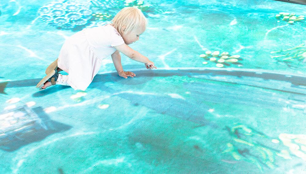 Lapsi pelaa led-screen-peliä lattialla.